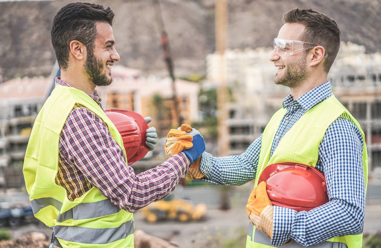 Builders on residential construction site making a deal – Happy workers are satisfied of their plan – Dealing, real estate, engineer, industrial and building houses concept – Focus on hands