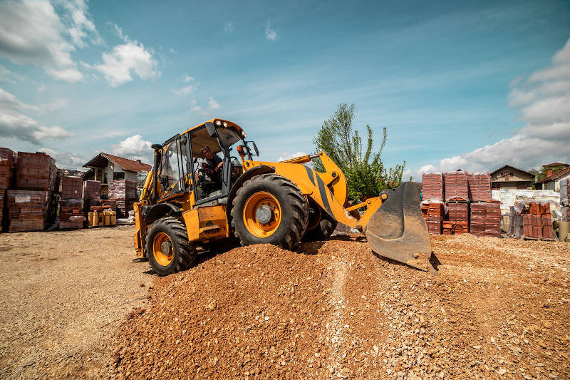 Yellow bulldozer excavator on the construction site working machine moving dirt